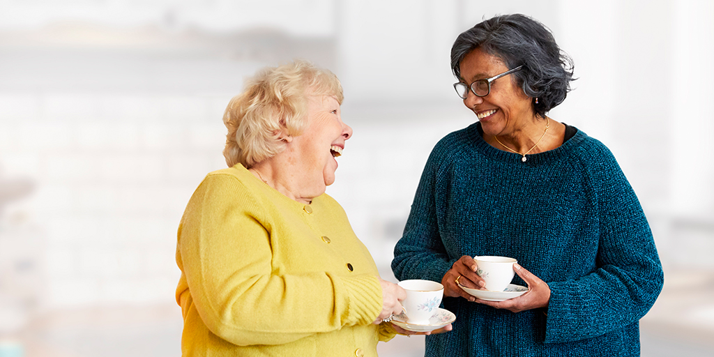 two women with cup of tea and laughing