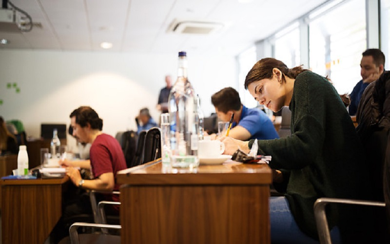 A student writing notes during a lecture