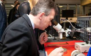 Jeremy Wright peering down a microscope.