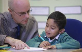 Boy writing at Reading Recovery lesson