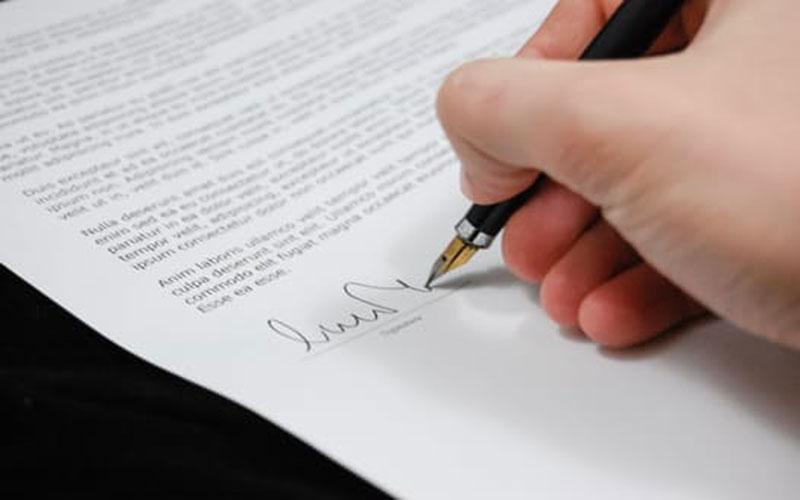 A person signs a contract document with a pen.