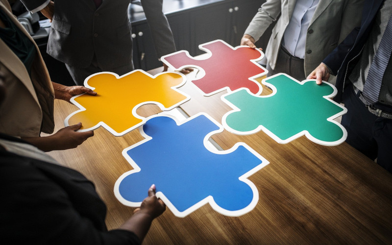People holding large jigsaw pieces