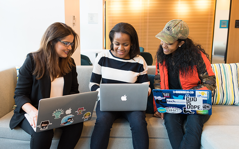 an image of three women sat on a sofa on their laptops