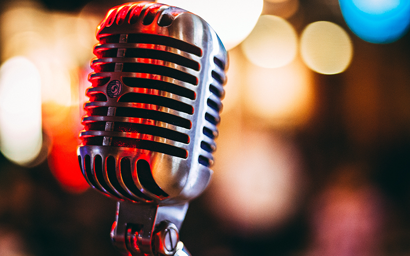 an image of a microphone with red and blue lights in the background