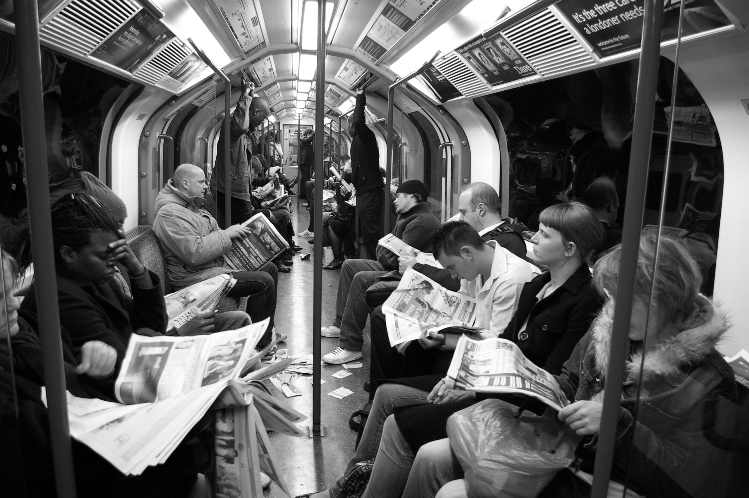 people reading newspapers on the tube