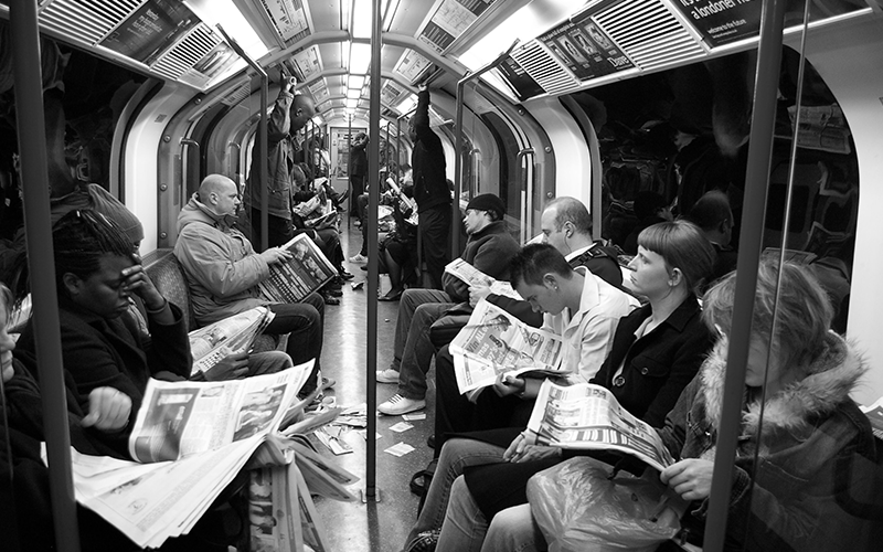 a black and white image of people sat on the tube