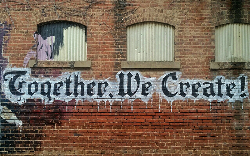 an image of graffiti saying 'together we create' on a brick wall