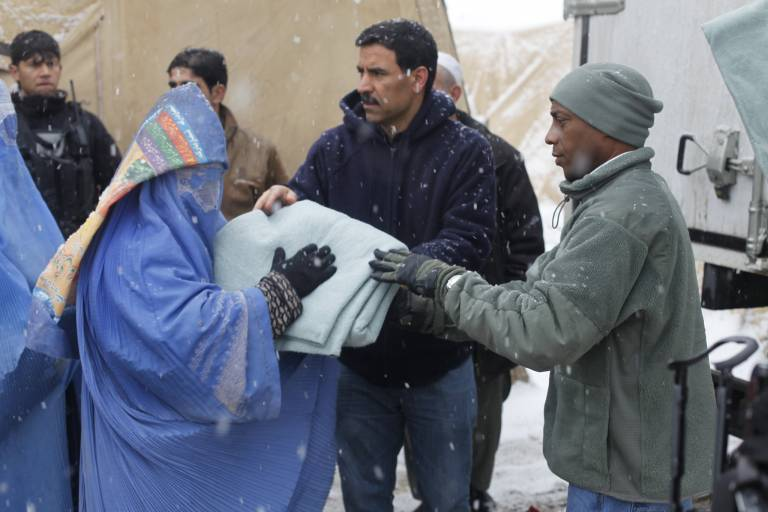 Refugees in Kabul, Afghanistan, receive aid from volunteers from the International Security Assistance Force