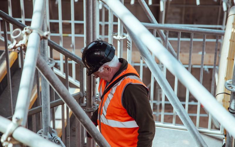 Man walking up stairs in hard hat