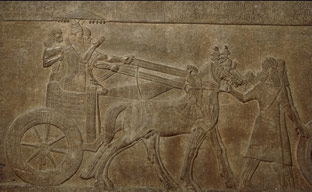 Stone panel showing king Tiglath-pileser standing on his chariot during a victory procession