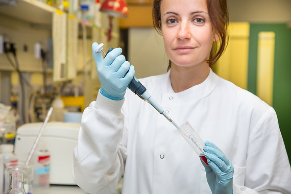 Woman scientist holding testtube in lab coat in a lab