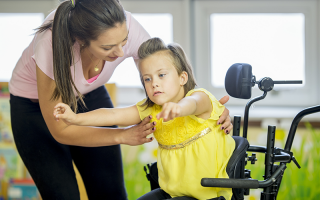 A caregiver is helping a little girl out of her wheelchair