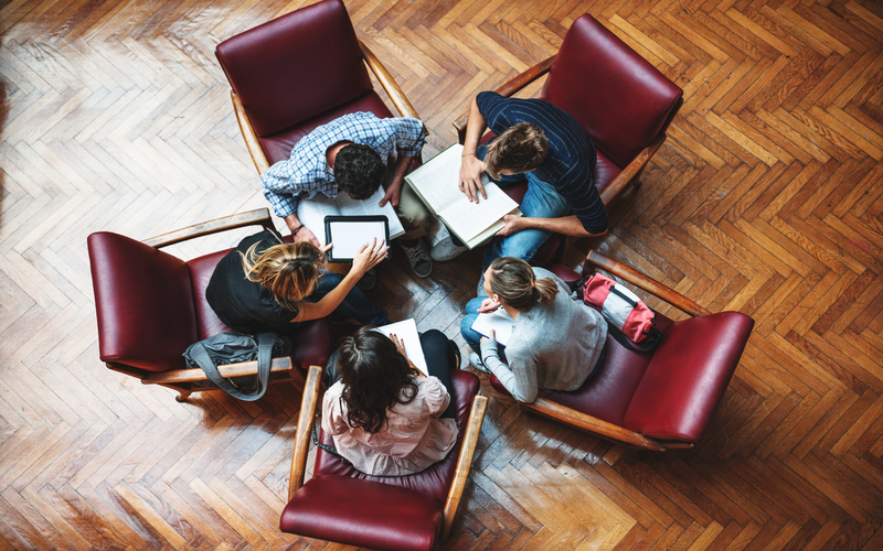 Ariel shot of four people sitting in a circle looking at paper