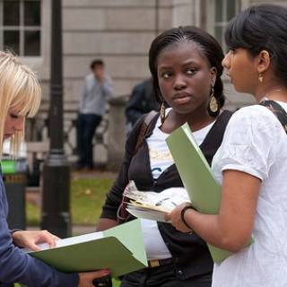 Three females reading and holding folders outside