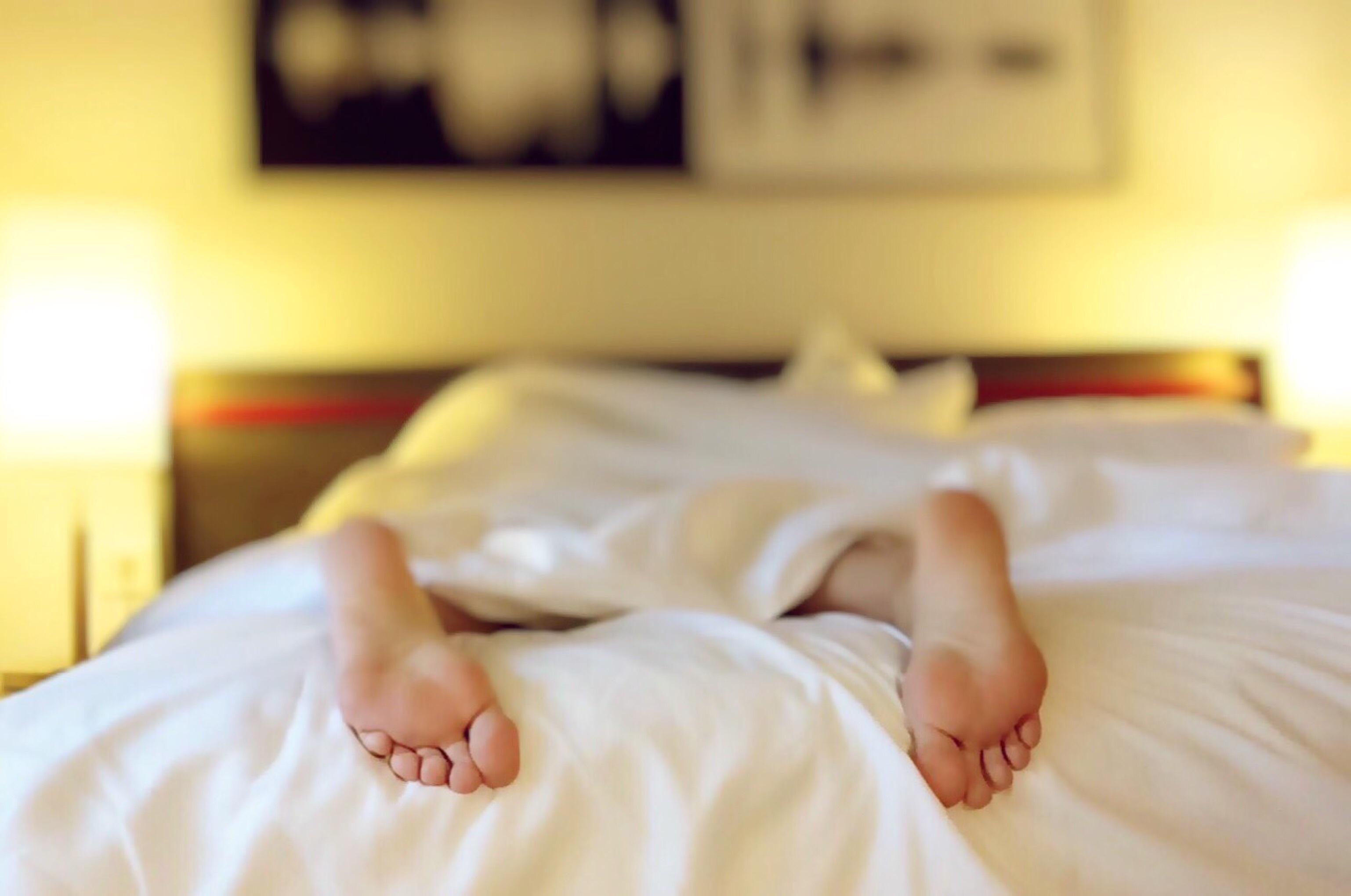 Feet poking out of white bed sheets