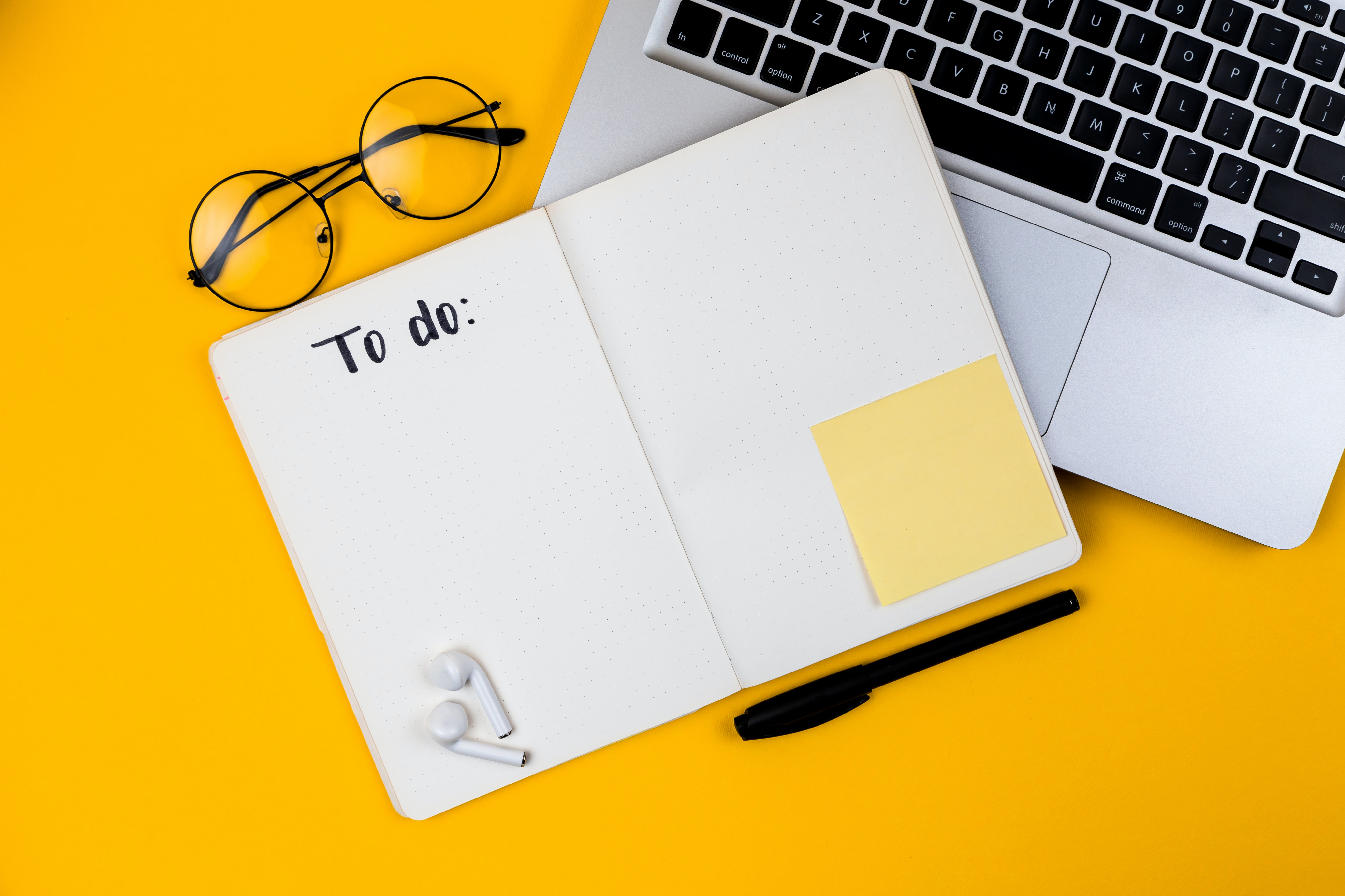 Notepad and glasses on yellow background