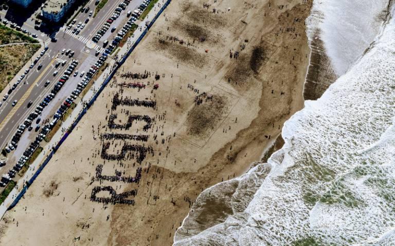 Aeriel shot of beach and people spelling resist