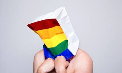 Image of man with rainbow bag on his head (photographer Christa Holka)