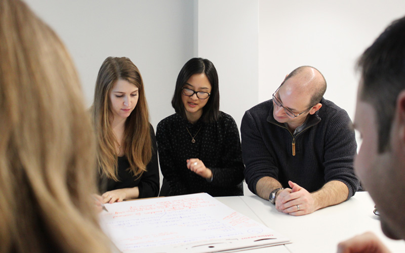 Colleagues discussing work at a desk