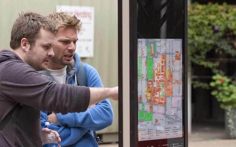 Students pointing at UCL map
