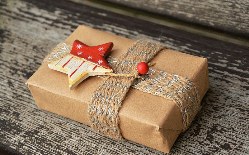 Present wrapped in brown paper with a ribbon and star on top.