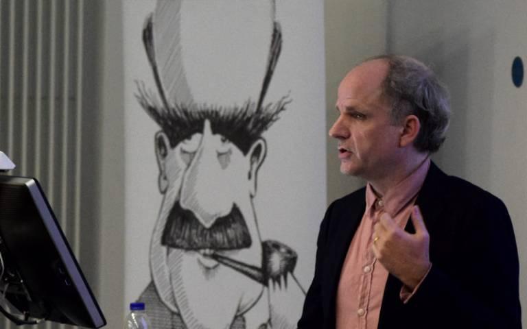 Prof. John Tresch, speaking in front of a caricature of JBS Haldane