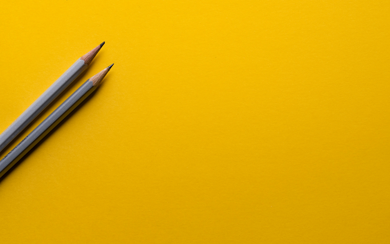 Two pencils yellow background