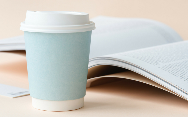 Blue coffee cup and open book