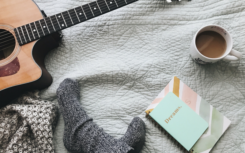 Notebooks, tea, woolly socks, guitar on bed.