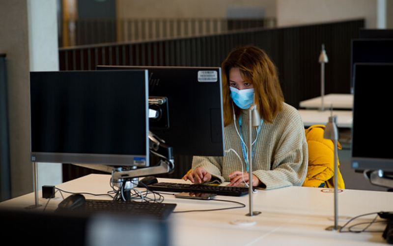 Female student wearing a mask looks at a computer