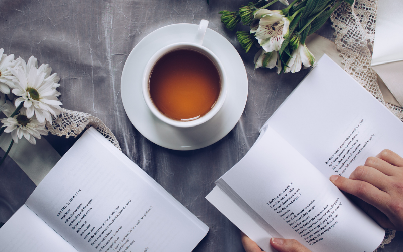 Two poetry books on a table, surrounded by flowers and a cup of tea