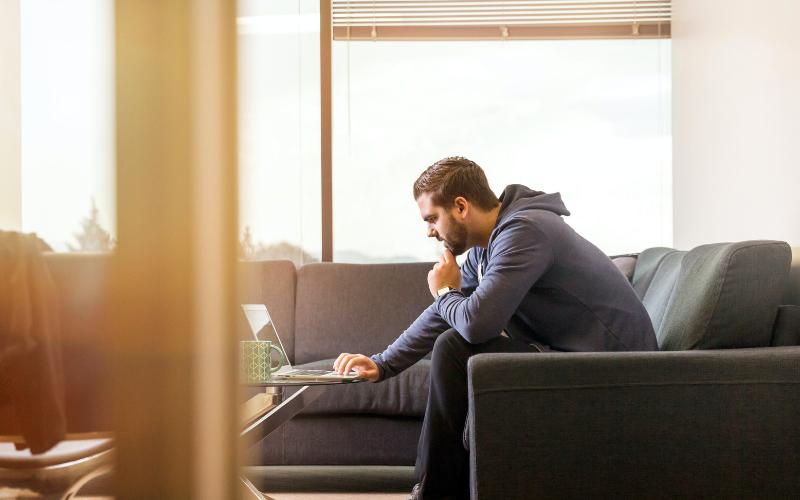 Man sitting on sofa looks at laptop