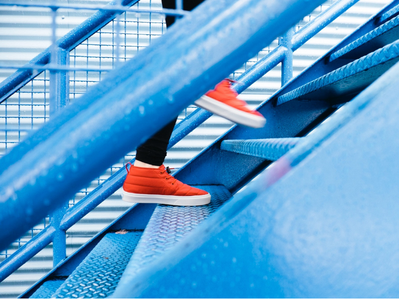 Person in orange trainers climbing blue stairs