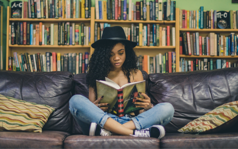 A woman reading on a sofa in front of a bookcase