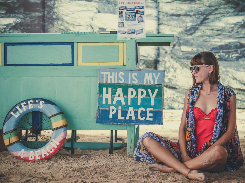 Woman sat on a beach with signs reading 'Life's a beach' and 'This is my happy place'