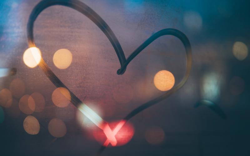 Heart shape drawn on window pane mist