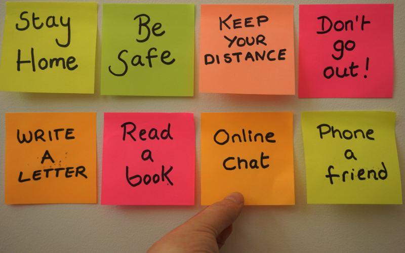 Post-it notes on a wall, reading 'Stay home', 'Be safe', 'Keep your distance', 'Don't go out!', 'Write a letter', 'Read a book', 'Online chat', 'Phone a friend'
