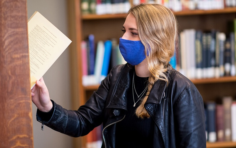 student taking book off library shelf