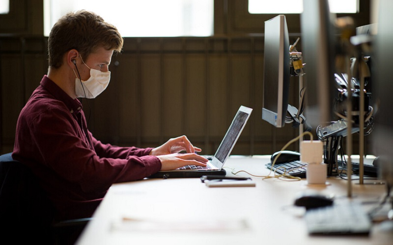 A student wearing a facemask sits at a desk on their laptop