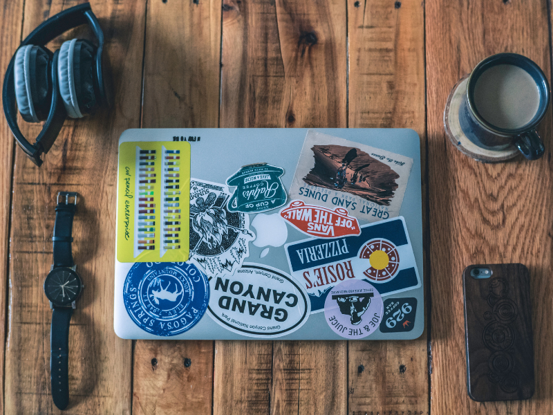 Laptop covered in stickers, headphones, coffee, watch and phone on desk