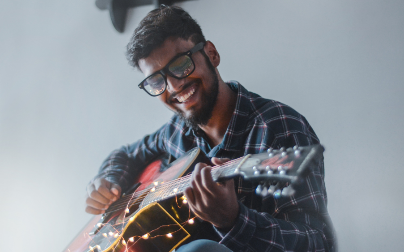 A man smiling while playing a guitar