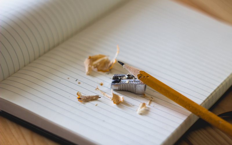 A pencil and a pencil sharpener on a notepad