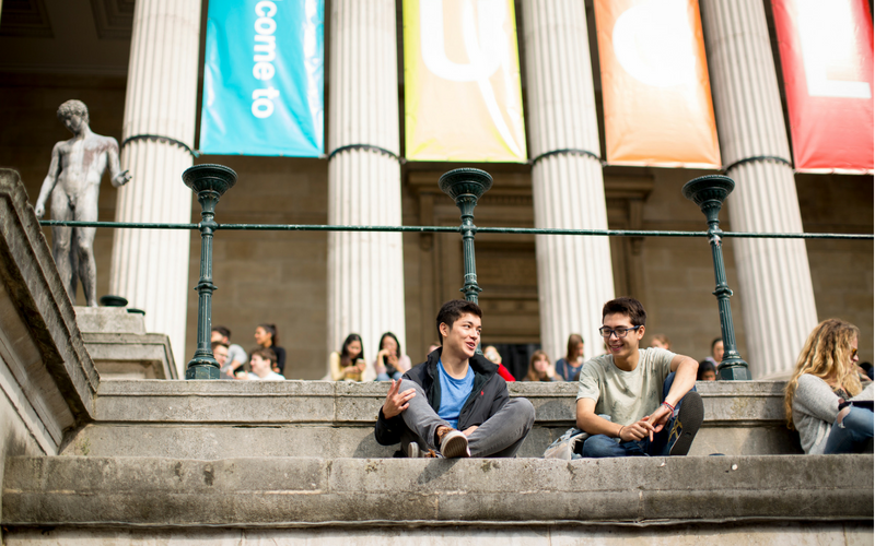 Two students sat on the Portico steps with welcome banners