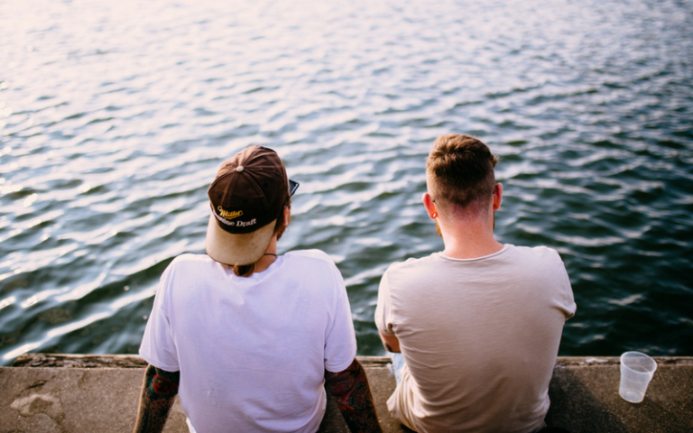 Two guy friends talking by the water