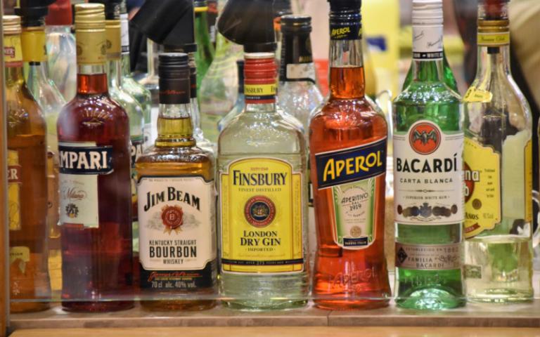 Selection of bottled alcohol spirits lined up on a shelf