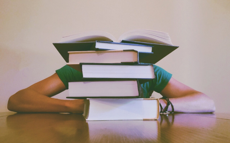 Person sitting at a desk behind a pile of books