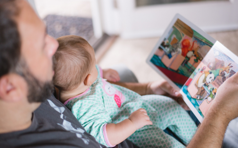 Parent reading story book to small child