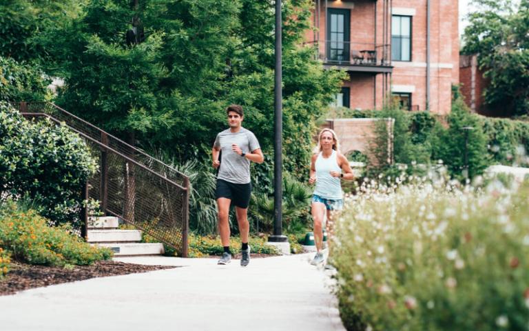 Man and woman running along a pavement