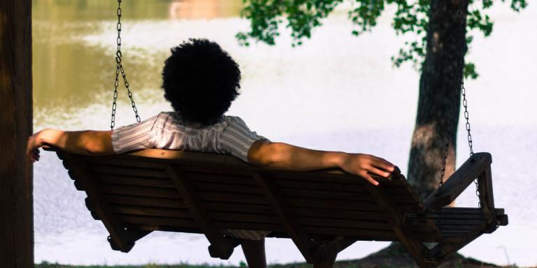 man relaxing on swing by lake