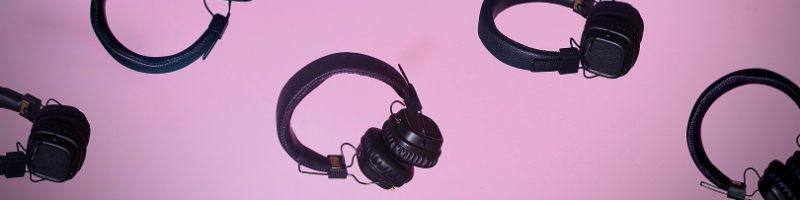 Several pairs of headphones on a colourful background